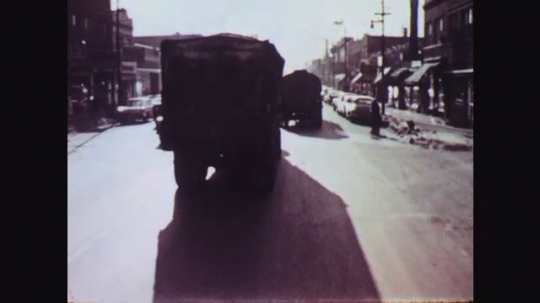 1950s: Fade into trucks driving down street in small city. Driver uses mirror to back up truck marked Norwalk Truck Lines. Gloved hand breaks seal on door. Man opens trailer doors. Truck backs up.