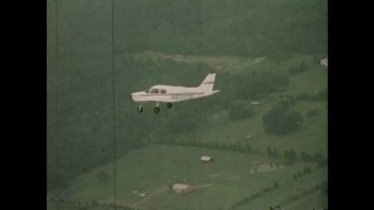 1970s: UNITED STATES: plane flies in sky over fields. Girl and man fly plane. Low pressure weather animation.