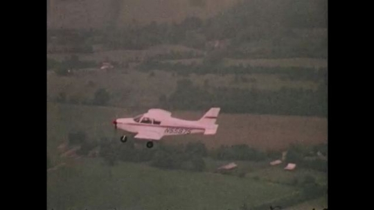 1970s: UNITED STATES: plane flies in sky over fields. Girl has flying lesson in plane.
