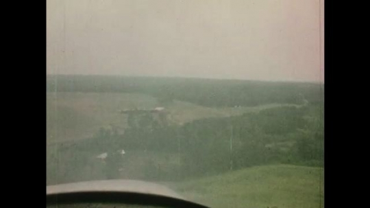 1970s: UNITED STATES: view of ground from plane. Girl in plane cockpit. Plane lands