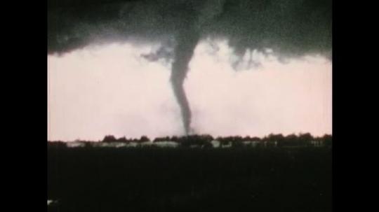 1970s: UNITED STATES: tornado forms above ground. Tornado crosses ground