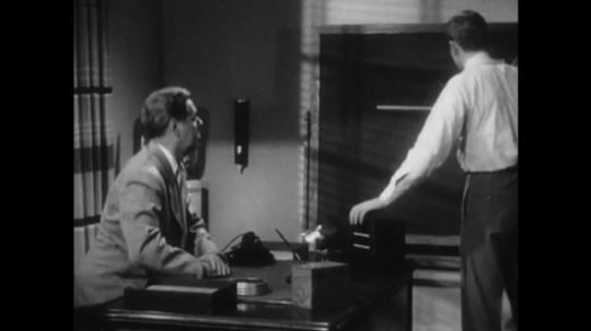 1950s: man in suit rises from desk and walks to blackboard as man in necktie points out chalk equation about radiation and a gauge and shakes hands.