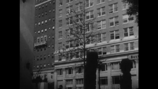 1950s: apartment building on city block. woman cooks in kitchen, sees blast and shelters in doorway. man reads in bedroom, jumps at flash and hides under bed. woman vacuums living room.