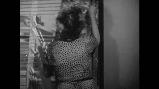 1950s: woman closes curtains over broken window. man and women talk in living room in front of horse painting.