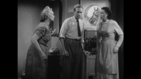 1950s: man and two women talk, woman in apron leaves and old woman walks away in living room near horse painting. woman puts down broom, looks at picture frame and races from bedroom.