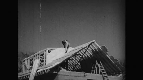 1950s: Man works on roof. Man works at building site. Garage door, Glass door