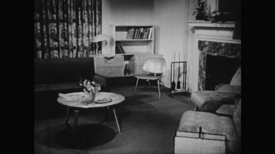 1950s: Wooden floor.  Well decorated room. Magazine on table