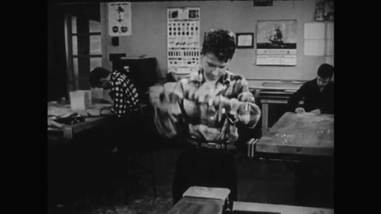 1950s: Boy works in classroom. Boy drills into material. hand uses hammer