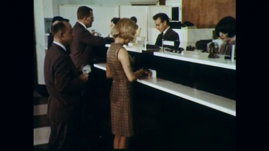 1960s: Inside bank, tellers help customers and others wait in line. Tellers and staff behind counter organize banking documents. Banker places stack of envelopes in sorting machine.