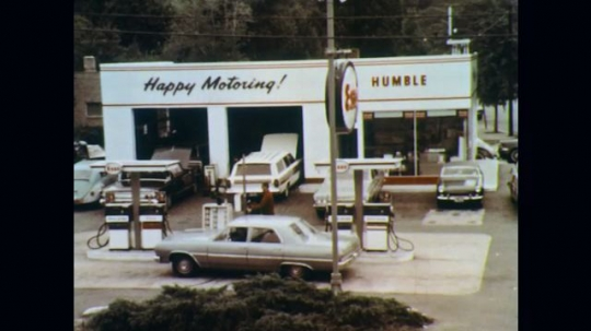 1960s: Man works at gas station. Model gas station view pulls out to show model town. View pulls back in to model gas station. Woman in white car briefly appears.