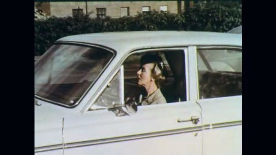 1960s: Woman sits in white car. Woman is next shown sitting at desk with man. Woman hands man a roll of documents from purse.