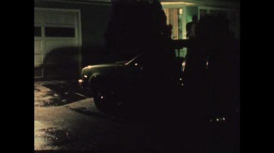 1970s: UNITED STATES: man leaves house. Man gets into car at night. Man starts engine