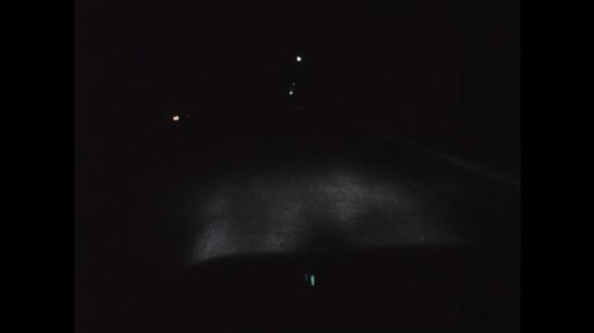 1970s: UNITED STATES: view through windscreen of car at night. Oncoming vehicle lights in street