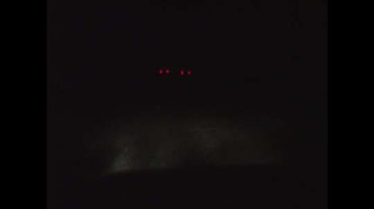 1970s: UNITED STATES: red lights of car in front at night. Cars on road at night.