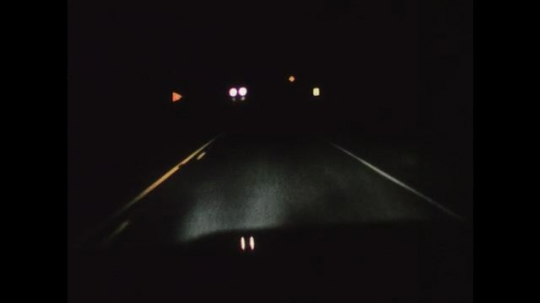 1970s: UNITED STATES: view through window of car at night. High beam light at night. View or urban environment at night.