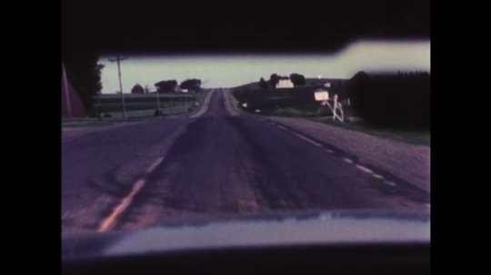 1970s: UNITED STATES: view through vehicle window on dark day and rain. Oncoming traffic on road. Car in city at night