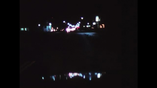1970s: UNITED STATES: blinding glare of lights at night. Oncoming vehicle lights. Car on road.