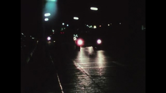 1970s: UNITED STATES: vehicle on road at night. Signs reflect night on road at night. Lane markings on highway. Pavement edge markings.