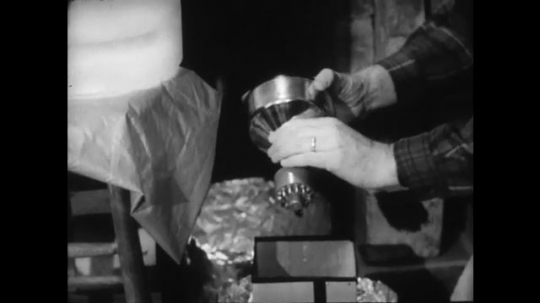 1960s: UNITED STATES: man picks up lamp. Man screws bulb.