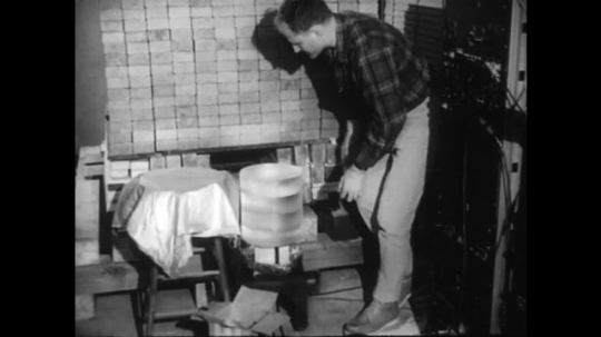 1960s: UNITED STATES: man sets up experiment. Man puts foil cover over container. Man speaks to camera
