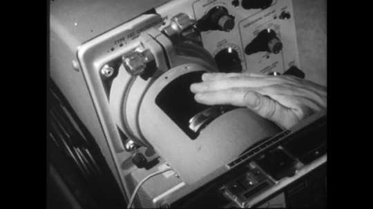 1960s: UNITED STATES: hands secure equipment in place with tape. Hand checks cable