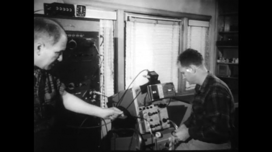 1960s: UNITED STATES: man speaks to camera. Man inspects machine.