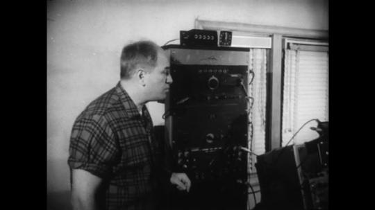 1960s: UNITED STATES: man speaks to camera. Man points to machine. Man prepares machine
