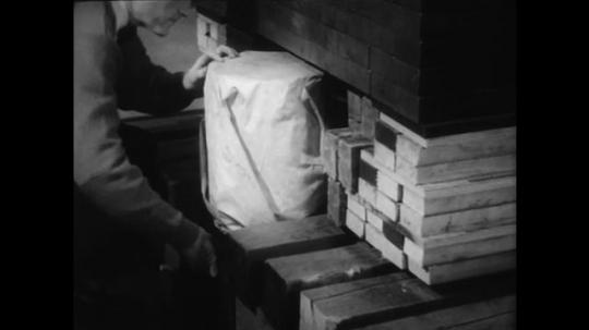 1960s: UNITED STATES: man puts equipment underneath construction. Man sets up equipment.