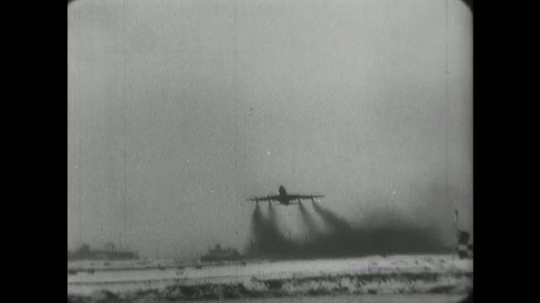 1960s: jet airplane lifts off from runway with four contrails and flies over street of small houses and powerlines.