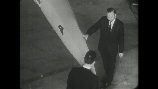 1960s: men talk, walk and touch nose and wing of supersonic jet airplane model in hanger.