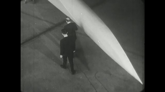 1960s: men talk, touch and walk around lockhead supersonic jet airplane with double delta wings model  from nose to wing.