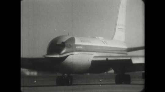 1960s: Boeing 727 jet airplane taxis, a man signals to stop and gas trucks arrive.