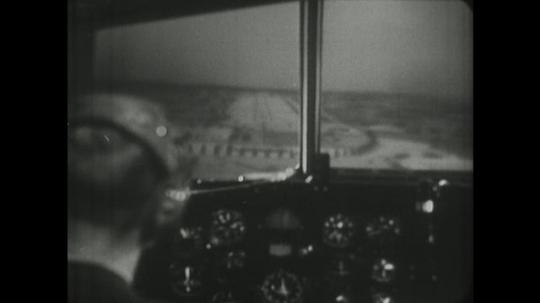 1960s: man in headset steers wheel in cockpit of jet airplane simulator as window view of airport runway shifts and steadies.