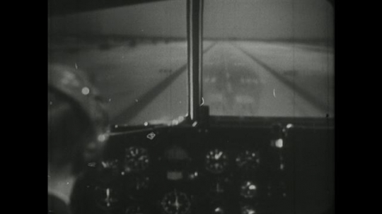 1960s: man in headset steers wheel in cockpit of jet airplane simulator, lands on airport runway and points at window.