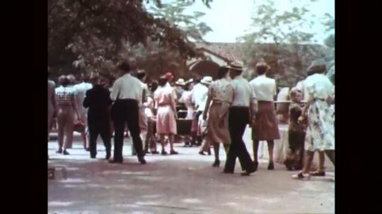 1950s: Crowd of people walk to enclosure. Two rhinoceros