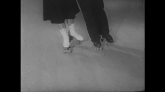1950s: UNITED STATES: male and female feet skate together.