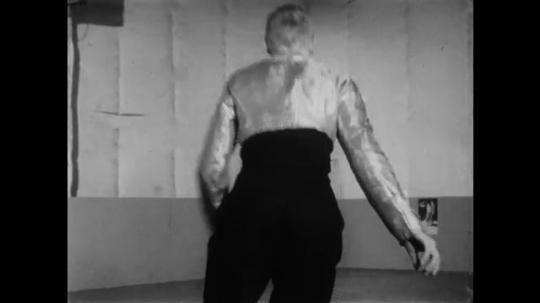1950s: UNITED STATES: man skates in rink in costume. Man spins in roller skates
