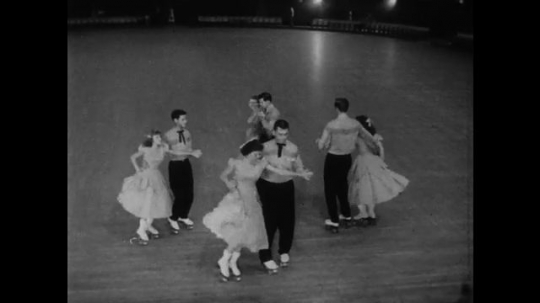 1950s: UNITED STATES: young people dance together in couples on skates. Couple skate backwards. Couples dance in skates