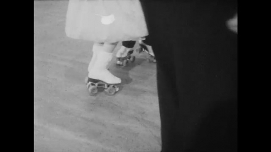1950s: UNITED STATES: close up of skaters feet. Boy and girl dance together in skates. Building and steps