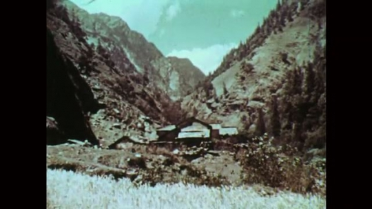 1950s: Village in mountain valley. Man places log on roof. Man places stone on roof