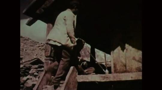 1950s: Men sit on platform. Men share pipe.