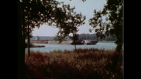 1970s: towboat pushes barges down river past riverbanks of trees. dam sits in water. man talks on microphone in boat cockpit. small building with stones for yard. flags of usa and army engineers.