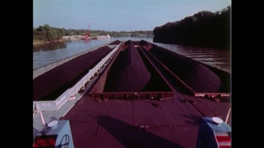 1970s: barges of coal float down river. man in boat cockpit steers wheel. towboat churns away. smokestacks smoke on factory near water as barge arrives.