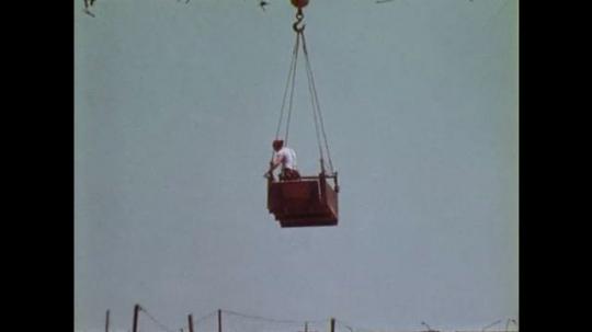 1970s: crane suspends man in bucket over metal bridge span under construction over dirt river bed. men work on railroad tracks. river flows under overpass.  men operate survey equipment.