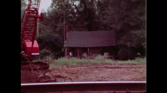 1970s: crane digs up dirt near railroad tracks and dumps inside grader near shack. man and woman sit and talk on bench in front yard of house.