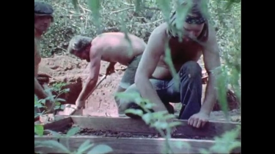 1970s: man with beard pushes dirt around large sift with trowel while other men dig in the woods. hand picks up stone. woman with bandana explores walls of deep long pit.