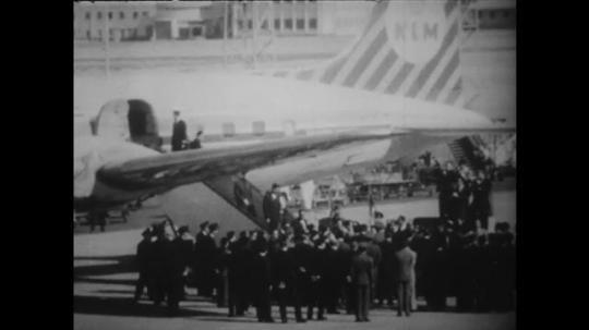 1960s: Crowd around plane. Zhao Enlai waving. Billboard. Photo of Zhao Enlai, pan to photo of Ayub Khan. Khan presenting gift to Zhao Enlai.