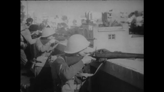 1960s: Soldiers fire from rooftop. Tank drives down street. Battle in street. Pan across destroyed buildings. Crowd gathered around ship.