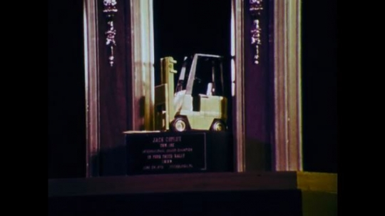 1970s: UNITED STATES: truck model on trophy. Man in hard hat. Man drives truck. Truck lifts boat.