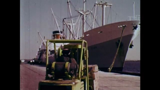 1970s: UNITED STATES: fork lift truck by ship. Man in glasses. Man drives truck. Man at steering wheel. Man drops boxes from truck